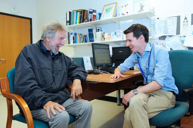 GP with elderly patient laughing