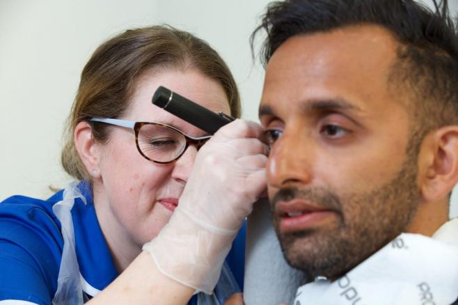 Female nurse looking in male's ear